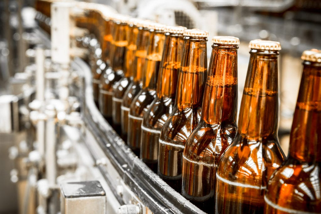 Beer bottles on conveyor belt, ready to be labeled
